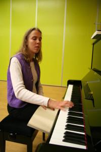 Kuvassa Riikka lukee pistenuotteja pianon ääressä.